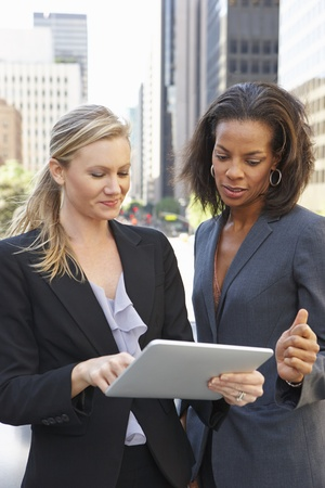african business people: Businesswomen Using Digital Tablet Outside Office
