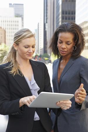two people talking: Empresarias que usa la tableta digital fuera de la oficina