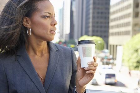 Businesswoman Drinking Takeaway Coffee Outside Office photo