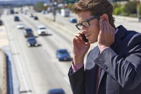 ruido: Hombre de negocios que habla en el tel�fono m�vil por autopista ruidosa Foto de archivo