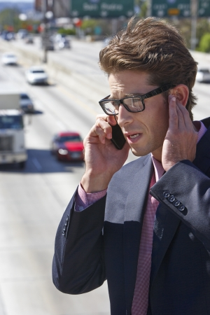 Businessman Speaking On Mobile Phone By Noisy Freeway photo