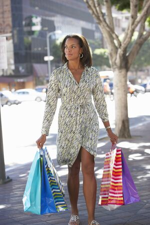 Woman Carrying Shopping Bags On City Street photo