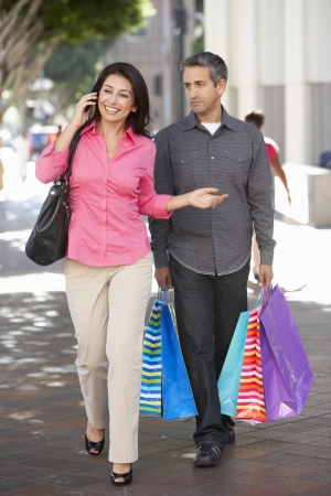 people walking street: Fed Up Man Carrying Partners Shopping Bags On City Street Stock Photo