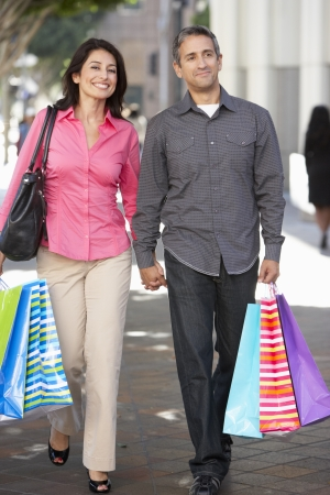 Couple Carrying Shopping Bags On City Street photo