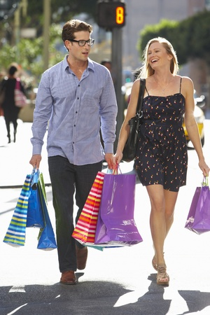 people walking street: Couple Carrying Shopping Bags On City Street