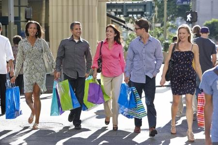 personas en la calle: Grupo de amigos que llevan bolsas de compras en la calle Ciudad