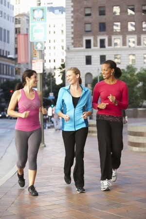 american city: Group Of Women Power Walking On Urban Street