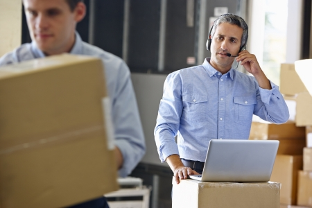 order shipment: Manager Using Headset In Distribution Warehouse
