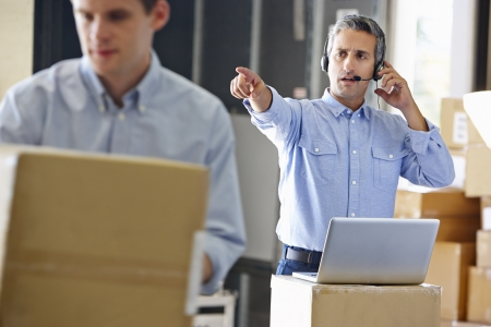 order shipping: Manager Using Headset In Distribution Warehouse