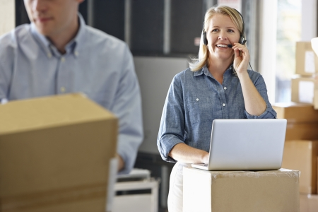 small business: Female Manager Using Headset In Distribution Warehouse