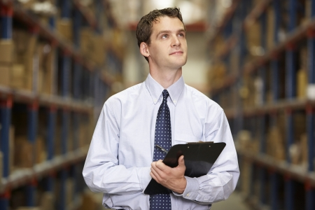 order shipment: Manager In Warehouse With Clipboard