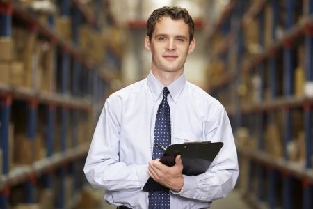 gestion empresarial: Retrato del encargado en el almac�n con el sujetapapeles