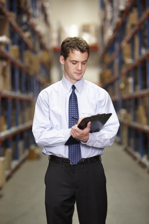 Manager In Warehouse With Clipboard photo