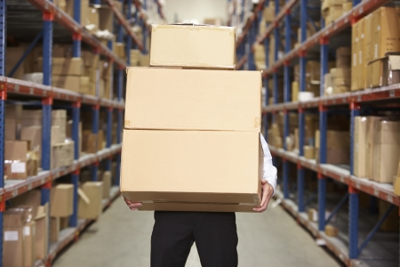 carrying: Man Carrying Boxes In Warehouse Stock Photo