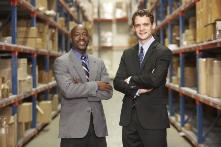 small business owner: Portrait Of Two Businessmen In Warehouse Stock Photo