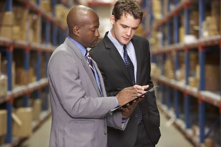 Two Businessmen Having Discussion In Warehouse photo