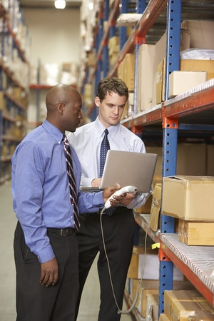 Two Businessmen With Laptop In Warehouse Stock Photo - 19530699