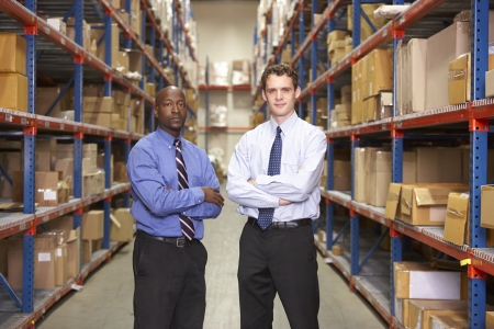 small business team: Portrait Of Two Businessmen In Warehouse Stock Photo