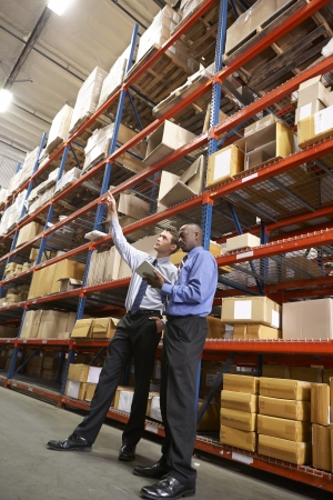order shipment: Two Businessmen With Digital Tablet In Warehouse