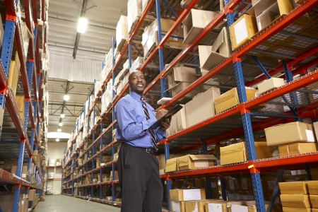 order shipment: Businessman With Clipboard In Warehouse Stock Photo