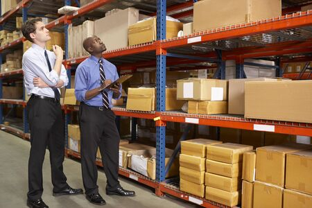 small business: Two Businessmen With Clipboard In Warehouse Stock Photo