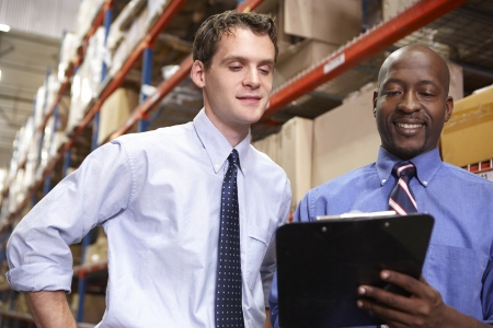 small business team: Two Businessmen With Clipboard In Warehouse Stock Photo