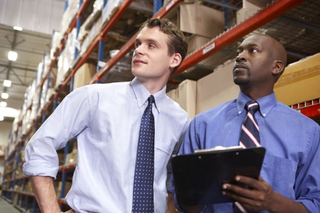 loading bay: Two Businessmen With Clipboard In Warehouse Stock Photo