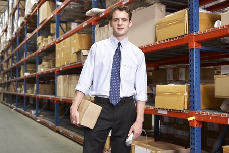 Businessman With Package And Scanner In Warehouse photo