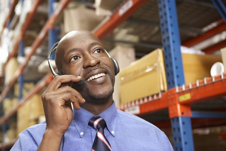 warehouse worker: Businessman Using Headset In Distribution Warehouse
