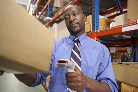 Businessman Scanning Package In Warehouse photo