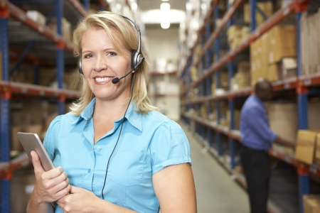 Businesswoman Using Headset In Distribution Warehouse photo