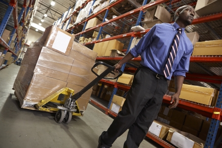 Man Pulling Pallet In Warehouse photo