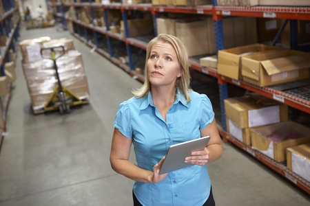 loading bay: Businesswoman Using Digital Tablet In Distribution Warehouse