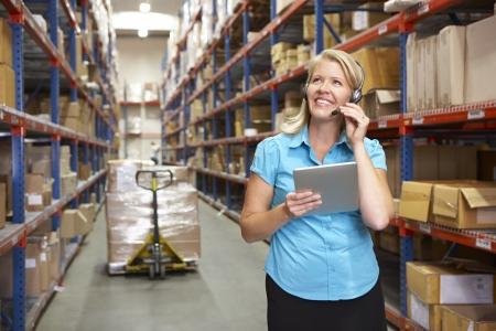 mobile headset: Empresaria que usa la tableta digital en el Almac?n de distribuci?n Foto de archivo