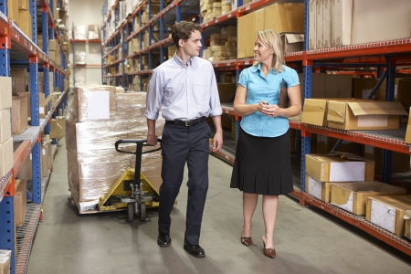 shrink wrapped: Businesswoman And Colleague In Distribution Warehouse