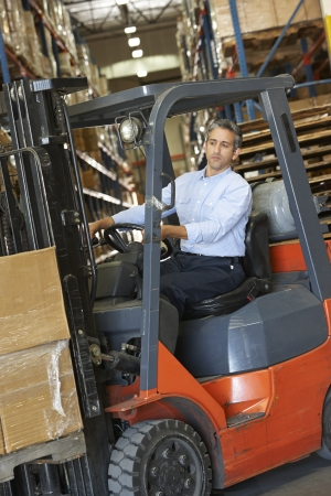 forklift driver: Man Driving Fork Lift Truck In Warehouse