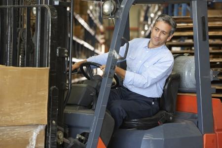 lift truck: Hombre que conduce Tenedor Lift Truck En Almac?n