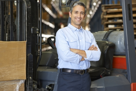 warehouse worker: Portrait Of Man With Fork Lift Truck In Warehouse