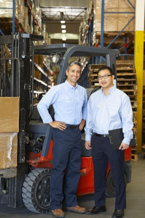 Portrait Of Businessmen With Fork Lift Truck In Warehouse photo