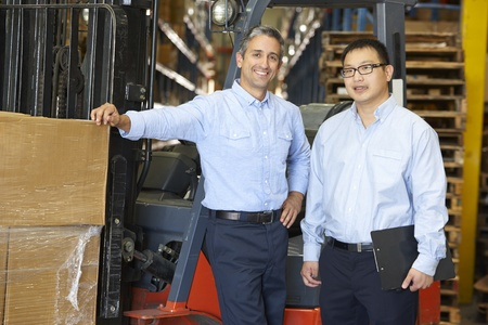 loading bay: Portrait Of Businessmen With Fork Lift Truck In Warehouse Stock Photo