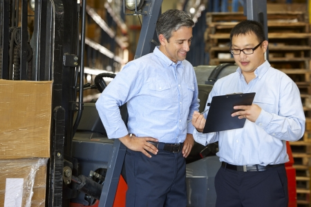warehouse worker: Businessmen Meeting By Fork Lift Truck In Warehouse Stock Photo