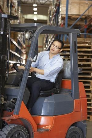 montacargas: Hombre que conduce Tenedor Lift Truck En Almacén