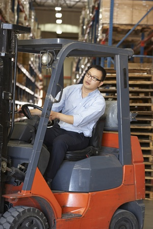 Man Driving Fork Lift Truck In Warehouse photo