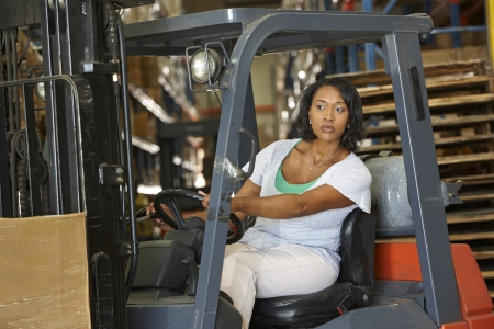 forklift driver: Woman Driving Fork Lift Truck In Warehouse Stock Photo