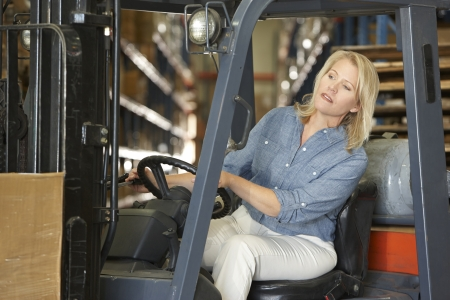 Woman Driving Fork Lift Truck In Warehouse photo