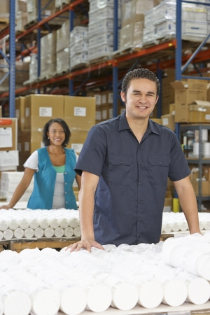 packaging industry: Factory Worker Checking Goods On Production Line Stock Photo