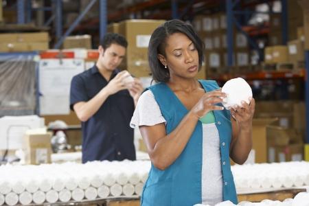 linea de produccion: Obrero Comprobaci�n de Productos en L�nea de Producci�n Foto de archivo
