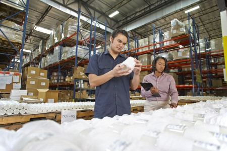 Factory Worker And Manager Checking Goods On Production Line photo