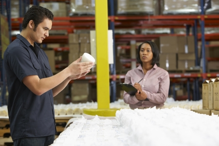 quality control: Factory Worker And Manager Checking Goods On Production Line