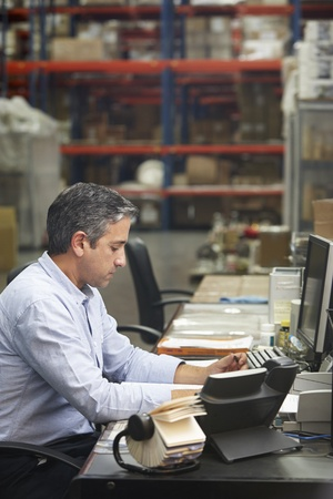 Manager Working At Desk In Warehouse Stock Photo - 19530528